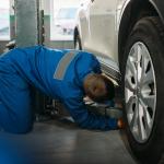 Elevador automotivo usado: um homem com macacão azul agachado olhando embaixo do carro.
