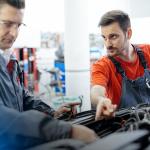 mecânica de automóveis - dois homens mexendo no motor de um carro