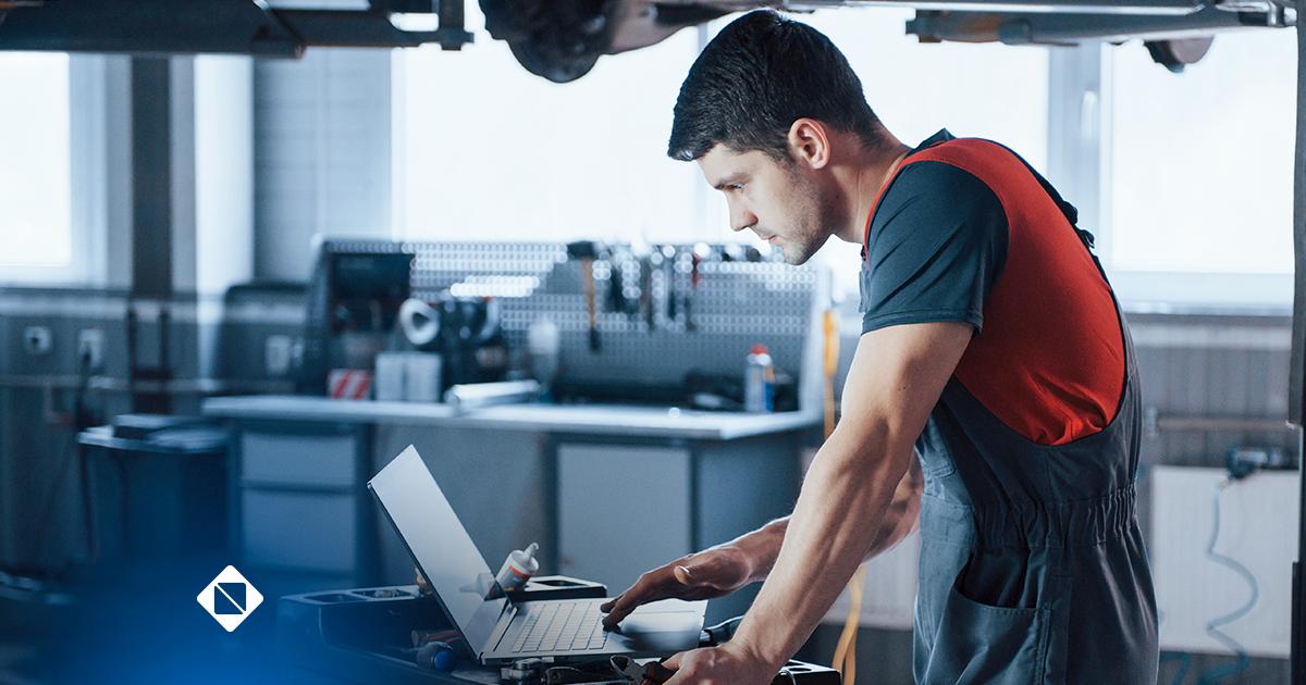 Oficina mecânica - na imagem há uma homem em pé olhando para o notebook em uma oficina mecânica representando que estão a gestão