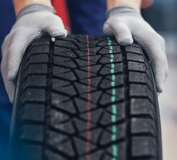 balanceadora de rodas - na imagem duas mãos com luvas brancas segurando um pneu